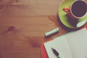 Laptop mit Tasse auf Schreibtisch
