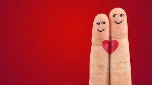 Zwei Finger, bemalt mit Gesicht, die sich wie ein Liebespaar aneinander schmiegen.