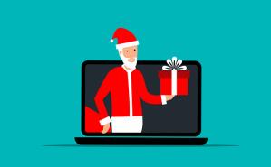 Weihnachtsmann, der aus Laptop heraus ein Geschenk überreicht