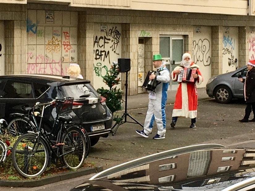 Weihnachtsmann mit Akkordeon auf der Straße.