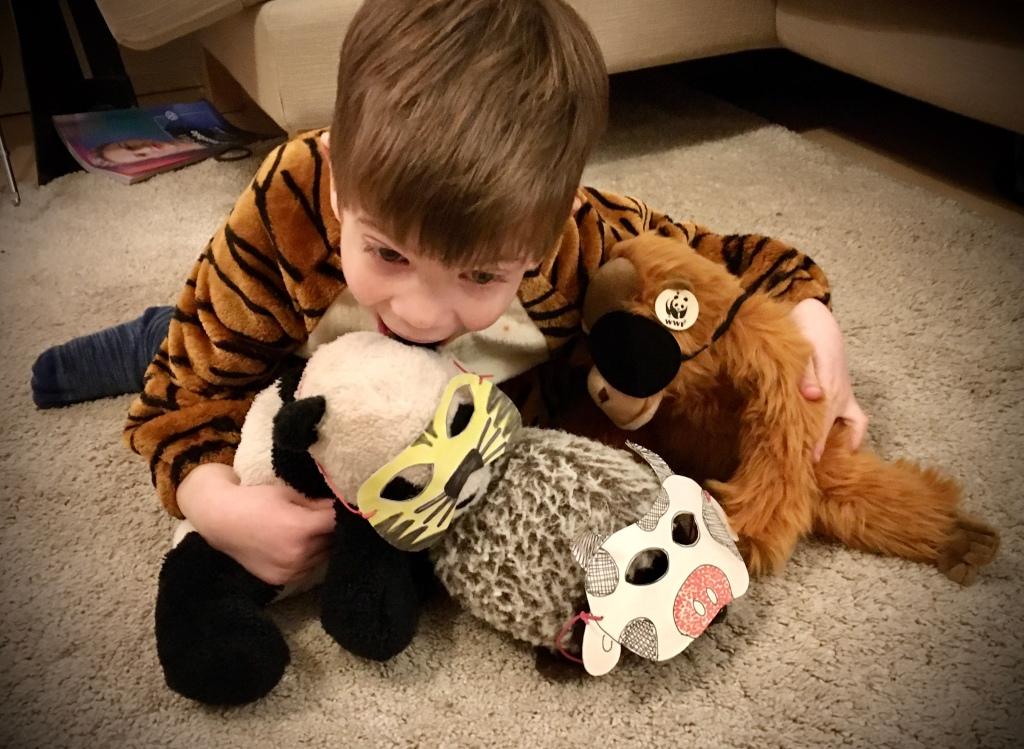 Kind mit Stofftieren, die Tiermasken tragen.