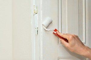 Frau, die Tür weiß streicht