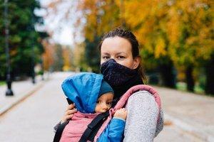 Frau mit Mund-Nasenbedeckung und Baby in der Trage