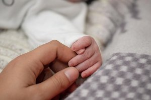 Hand eines Erwachsenen hält die Hand eines Neugeborenen.