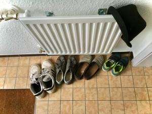 Unterschiedlich große Schuhe in einer Reihe, von oben fotografiert.