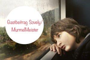 Junge schaut bei Regenwetter traurig aus dem Fenster.